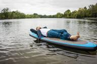 Businessman lying on SUP board on a lake - JOSF03797