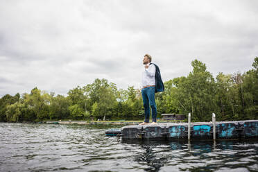 Businessman standing on a float a lake looking out - JOSF03800