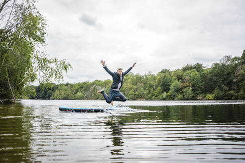 Businessman jumping from SUP board into a lake - JOSF03803