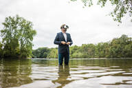 Businessman standing in a lake wearing VR glasses - JOSF03809