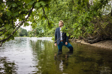 Businessman standing in a lake looking out - JOSF03812