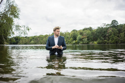 Businessman standing in a lake with cell phone - JOSF03815