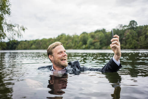 Mad businessman holding cell phone inside a lake - JOSF03818