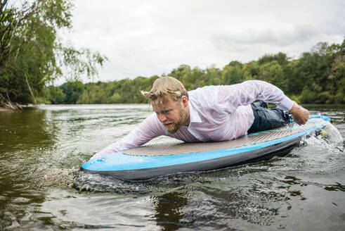 Wet businessman lying on SUP board on a lake - JOSF03821