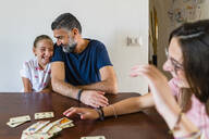 Happy father with two daughters playing cards on wooden table at home - MGIF00702