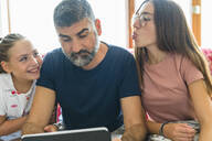 Father with two daughters looking at tablet on couch at home - MGIF00705
