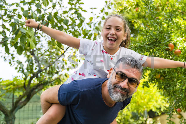 Father carrying happy daughter piggyback in garden - MGIF00720 - Giorgio Magini/Westend61