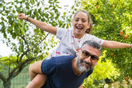 Father carrying happy daughter piggyback in garden - MGIF00720
