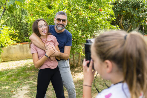 Girl taking a picture of happy father with daughter in garden - MGIF00723