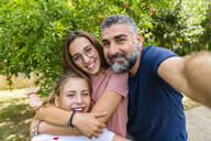 Happy father with two daughters taking selfie in garden - MGIF00729