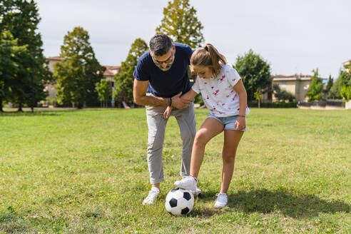 Father and daughter playing football on a meadow - MGIF00732