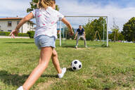 Father and daughter playing football on a meadow - MGIF00735