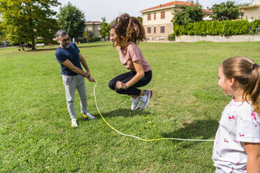 Father with daughter holding rope for girl skipping - MGIF00738