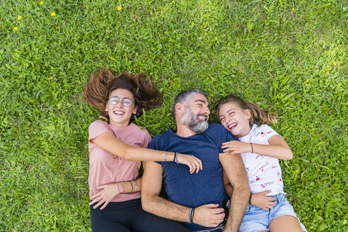 Happy father with two daughters lying on a meadow - MGIF00741