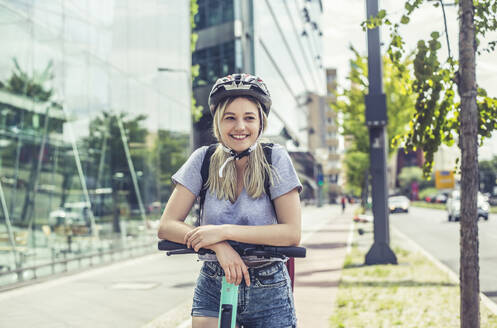 Portrait of smiling young woman  wearing cycling helmet leaning on handlebar of E-Scooter - BFRF02075