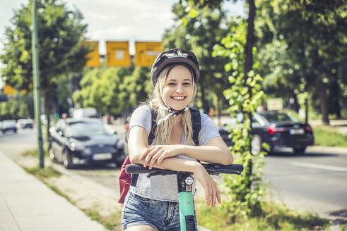 Portrait of happy young woman  wearing cycling helmet leaning on handlebar of E-Scooter - BFRF02084