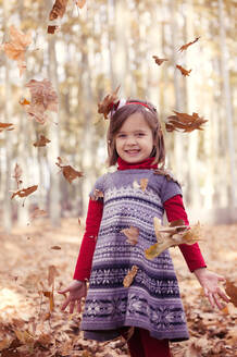 Smiling girl standing in autumn forest - XCF00259