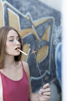 young woman lighting cigarette with a sparkler - JPTF00336