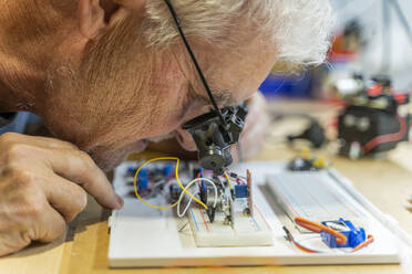 Senior man working on electronic circuits in his workshop - AFVF04016