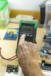 Senior man working on electronic circuits in his workshop, close up - AFVF04019