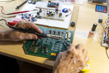 Senior man working on electronic circuits in his workshop, close up - AFVF04025