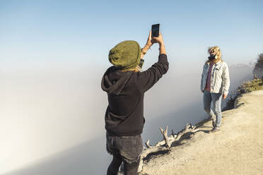 Young woman with respirator mask taking a photo of her girlfriend at the edge of volcano Ijen, Java, Indonesia - KNTF03600