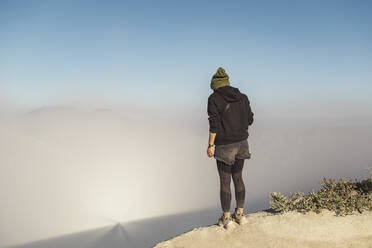 Young woman standing at the edge of volcano Ijen, Java, Indonesia - KNTF03603