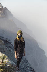 Young woman with respirator mask standing at the edge of volcano Ijen, Java, Indonesia - KNTF03606