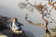 Woman with respirator mask sitting at volcano Ijen, Java, Indonesia - KNTF03609