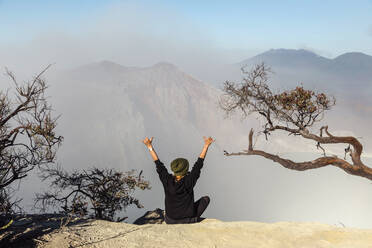 Woman with respirator mask sitting at volcano Ijen and  raising her arms, Java, Indonesia - KNTF03612