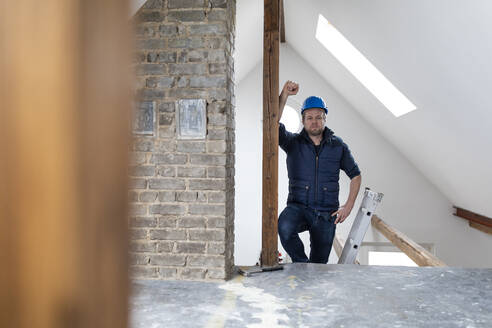 Architct standing on construction site of a loft conversion - GUSF02656