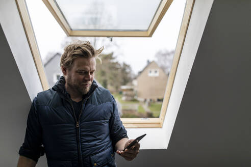Architect reading message on his mobile phone - GUSF02659