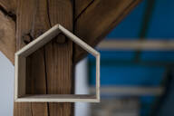 House shape handing on timber of a roof truss - GUSF02665