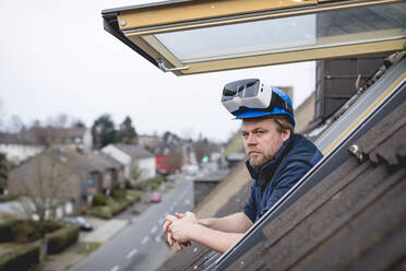 Architect with VR goggles on his safety helmet, looking out of rooflight - GUSF02674