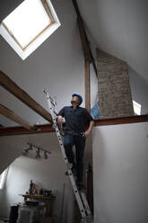 Architect working on construction sit of a loft conversion, standing on ladder - GUSF02680