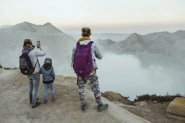 Family with respirator masks standing at the edge of volcano Ijen, Java, Indonesia - KNTF03615