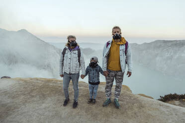 Family with respirator masks standing hand in hand at the edge of volcano Ijen, Java, Indonesia - KNTF03618