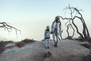 Mother and son with respirator masks standing hand in hand at the edge of volcano Ijen, Java, Indonesia - KNTF03621