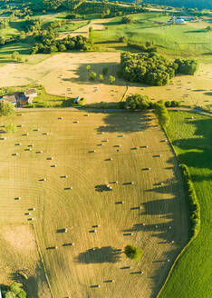 Aerial view of tractor harvesting straw bales in field in Correze, France. - AAEF03701