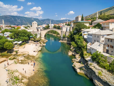 People at Old Bridge over Neretva river in Mostar, Bosnia and Herzegovina. - AAEF03935