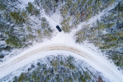 Aerial view of a car driving in the snow in the forest of Estonia - AAEF04040