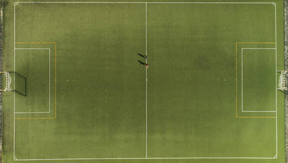 Aerial view of a two players training on synthetic surface football pitch on a summer day. - AAEF04235