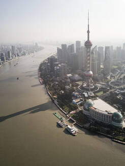 Aerial view of Shanghai skyline with Oriental Pearl Tower in foreground with passing Huangpu river, China. - AAEF04460