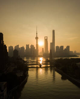 Aerial view of Shanghai skyline at sunset with passing Huangpu river, China. - AAEF04463