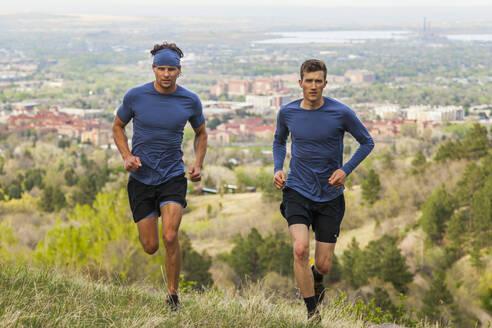 Men run through meadow in Chautauqua above Boulder, Colorado - CAVF63380