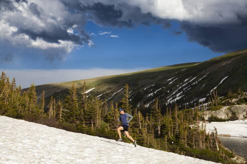 Man trail runs on snow in Indian Peaks Wilderness, Colorado - CAVF63401