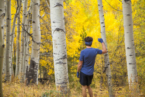 Man on trail run leans on aspen with fall colors in Vail, Colorado - CAVF63425