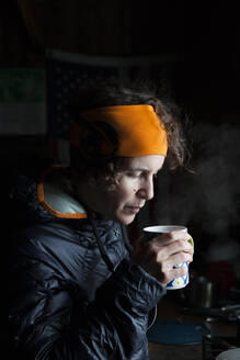 Woman skier sips hot tea inside backcountry cabin - CAVF63464