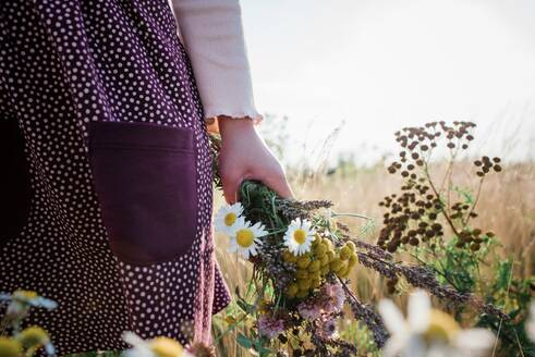 Young girls hand holding a bunch of wildflowers in a meadow at sunset - CAVF63662
