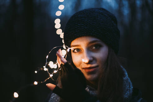 Close up portrait of beautiful young woman holding Christmas lights - CAVF64259